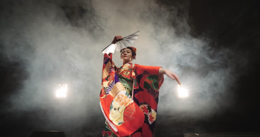 4K beautiful Japanese geisha dancing on stage and posing for the camera,the smoke in the background, slow motion