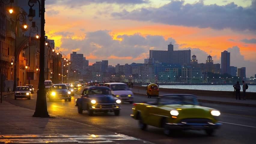 Cuba, Havana, Centro Habana, the Malecon, Vedado skyline at sunset, classic 1950's American cars
