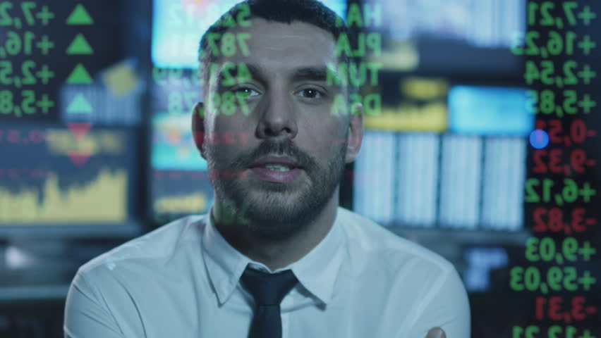 Stockbroker is looking at data with numbers on a transparent glass screen in a dark office filled with displays. Shot on RED Cinema Camera in 4K (UHD).
