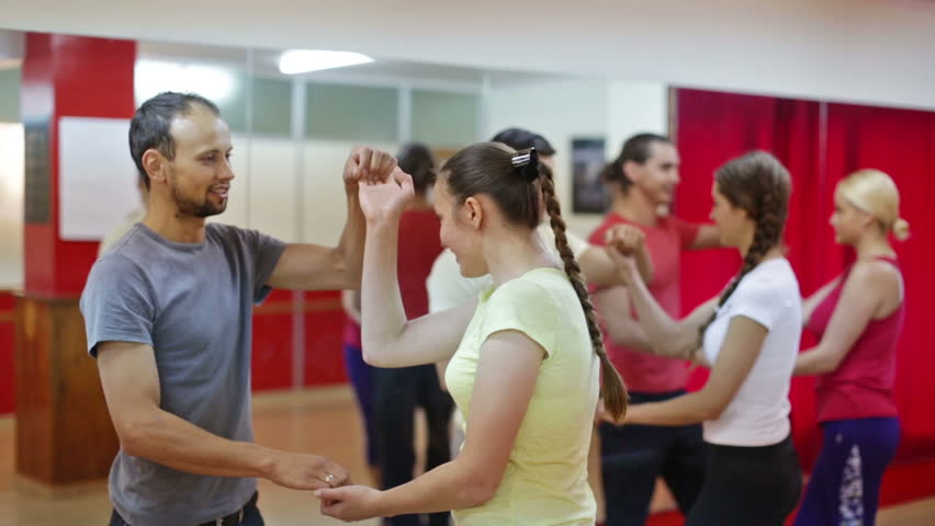Smiling adults dancing salsa together in dance studio