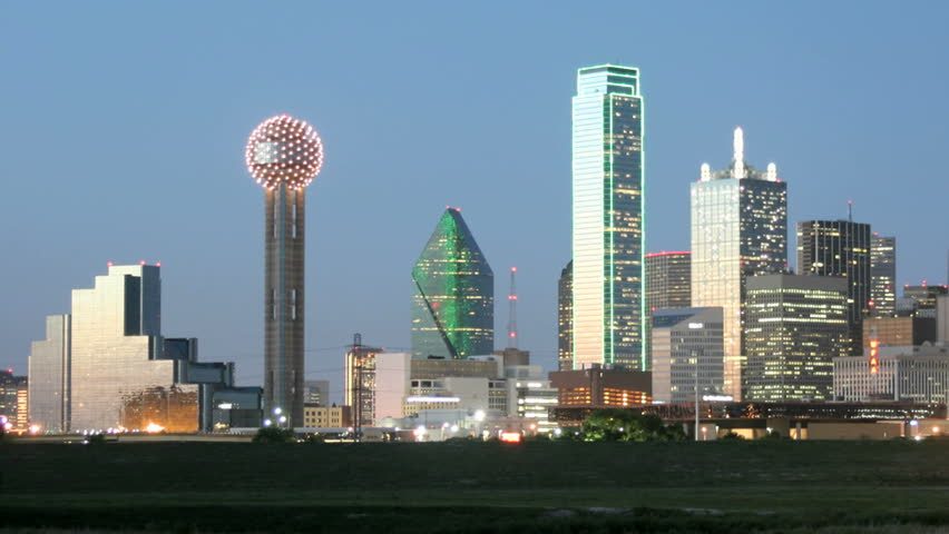 Slow pan of city lights illuminating the Dallas skyline at night.