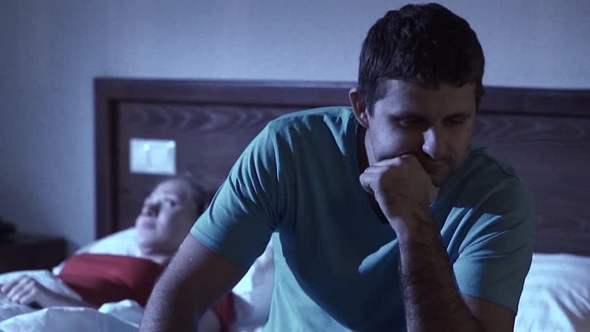 Upset man having impotence problem sitting on the bed with his girlfriend