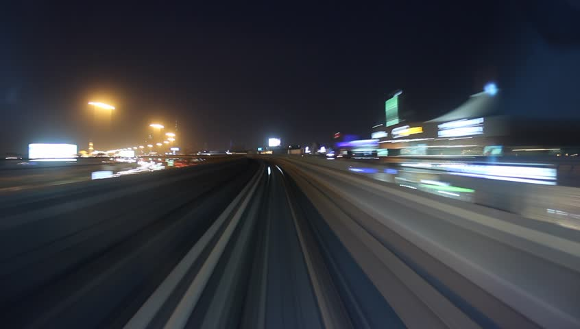 Modern driver-less metro train rush forward, along night Dubai, front cabin POV view, smooth time-lapse shot. Overground railway, dark low rise buildings around, bright road lights at night | Shutterstock HD Video #14493034