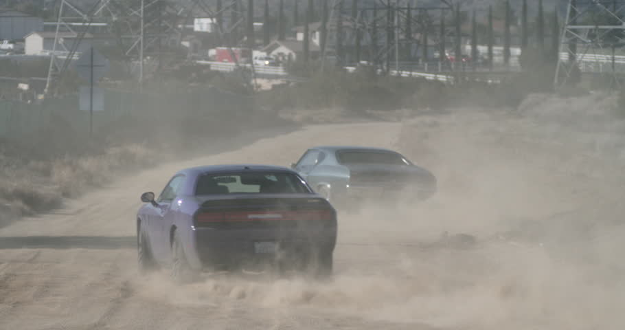 SLOW MOTION cars in desert car chase speed along dirt road away from camera, kicking up dust, as helicopter pursues above