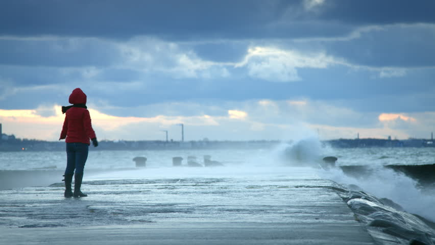 Woman standing near storm waves hitting the pier | Shutterstock HD Video #14500486
