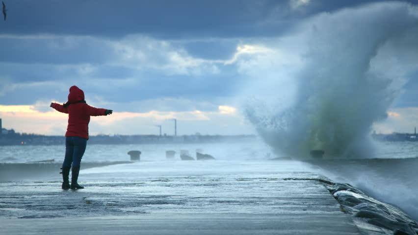Woman standing near storm waves hitting the pier | Shutterstock HD Video #14500486