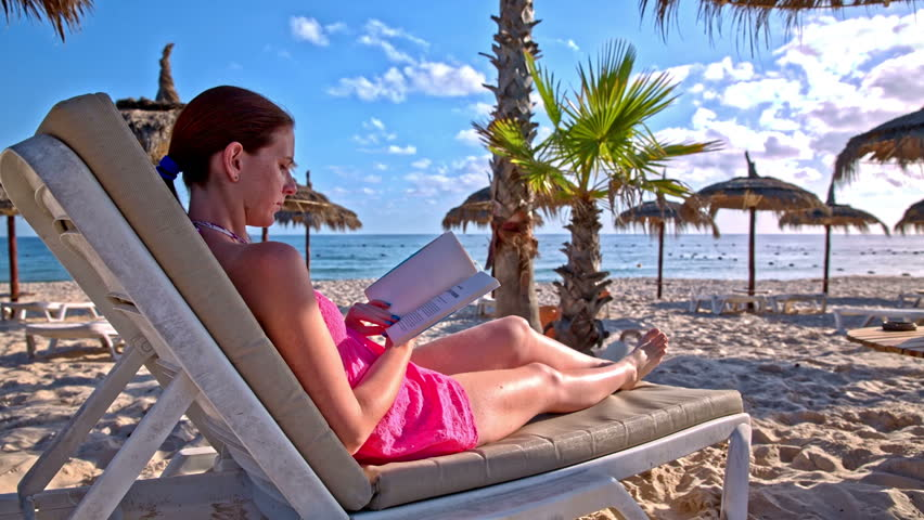 Reading book and entertained by a cat on the beach. Woman lying on lounger and reading a book at a beautiful beach. A white cat jumping on the sand around umbrellas. | Shutterstock HD Video #14504962