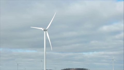 white windmill blades power energy clouds