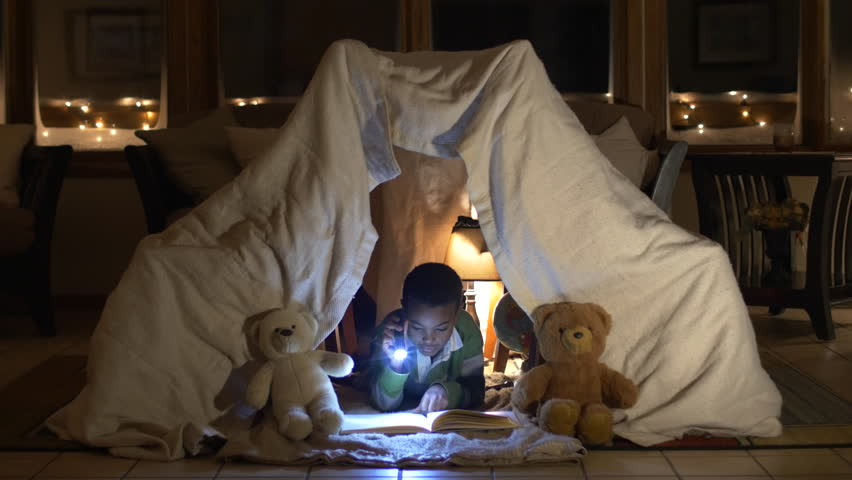 Boy in blanket fort reading book at night.