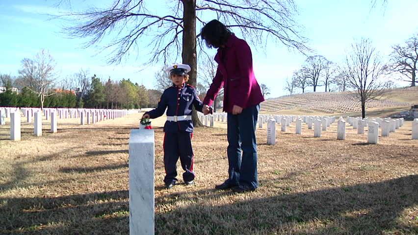 Young boy kneeling by father's grave to give honor to fallen solider hero. Small child sad over loss of his military dad in combat.