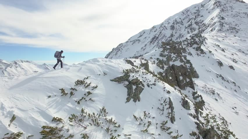 Young Man Walking Up Mountain Slope Backpacking Winter Hike Extreme Conditions Swiss Alps  Aerial Drone Flight Footage  | Shutterstock HD Video #14596516