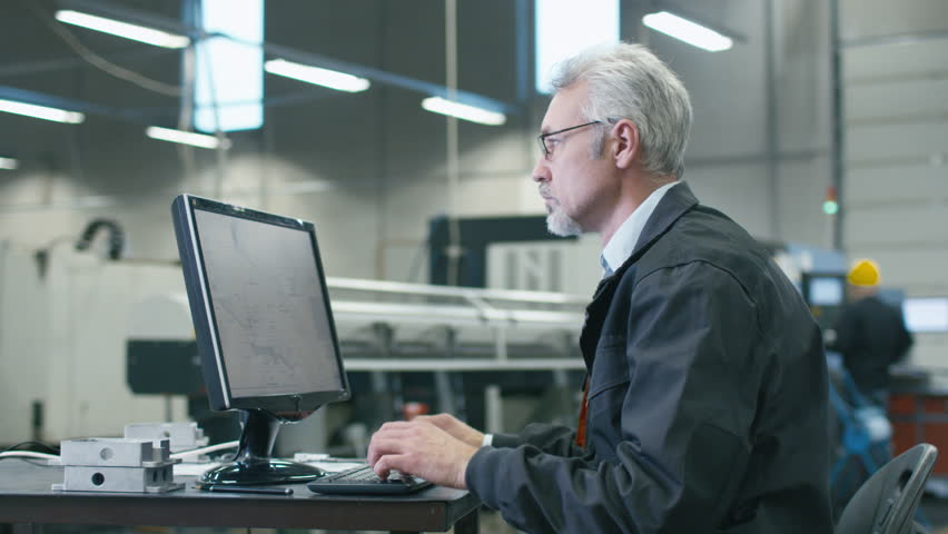 Senior engineer in glasses is working on a desktop computer in a factory. Shot on RED Cinema Camera in 4K (UHD).   Shutterstock HD Video #14602708