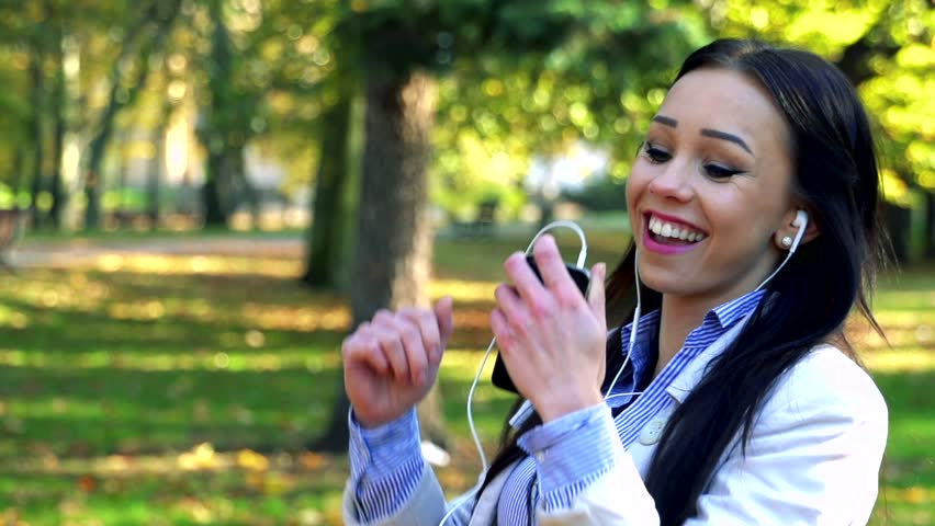 Slowmotion young beautiful woman stands in park, listens to music from mobile ale dances   Shutterstock HD Video #14602744
