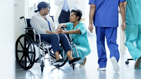 African American female nurse and patient on wheelchair consult in hospital