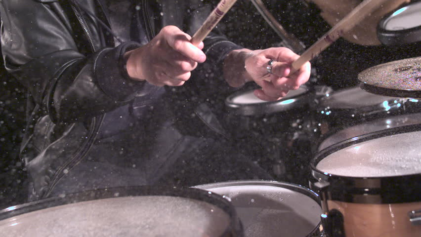 EXTREME SLOW MOTION hands rapidly play drum set, splashing water drops as camera moves to side