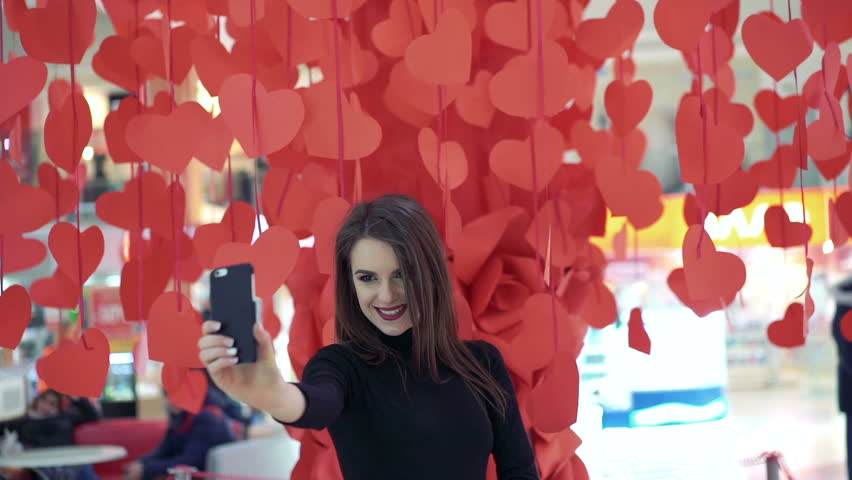 Pretty lady posing and taking selfie on the background of red hearts. Happy. | Shutterstock HD Video #14644630