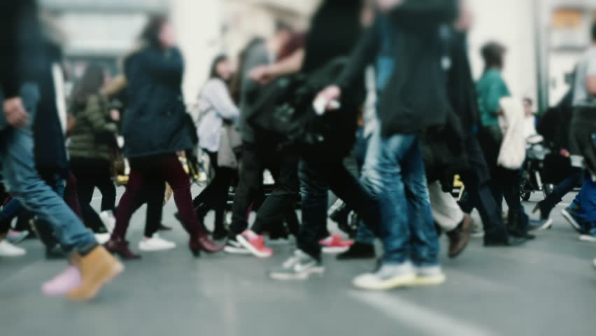 People pedestrians walk/cross big city intersection slow motion 100p.Gimbal stabilized tracking shot of an anonymous crowd mostly of young age getting across a busy city street.No logos/faces visible.