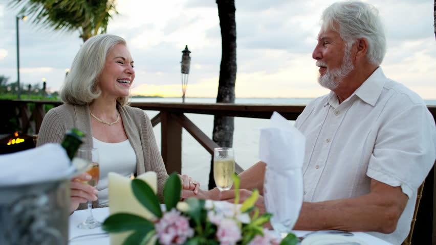 Retired Caucasian senior couple enjoying evening dinner at luxury beach hotel