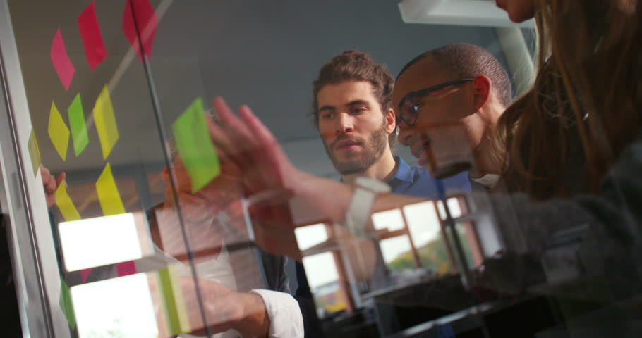 Brainstorming session of multi-ethnic start up team. African-american team member explaining business idea to businessman in office | Shutterstock HD Video #14698249