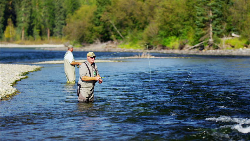Fisherman using rod and reel casting line in freshwater river Canada #14711608