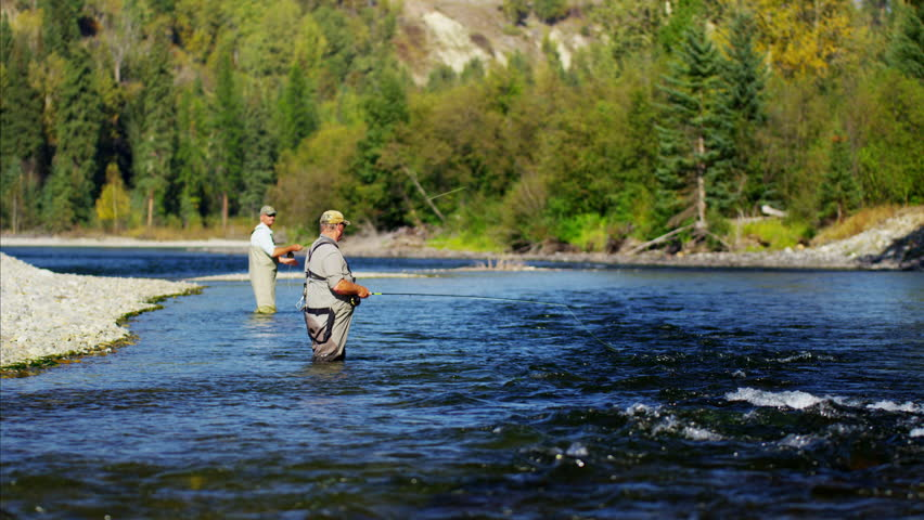 Fisherman using rod and reel casting line in freshwater river Canada #14711614