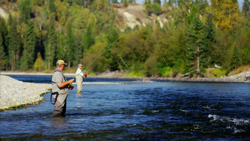 Fisherman using rod and reel fly fishing in freshwater river USA #14711944