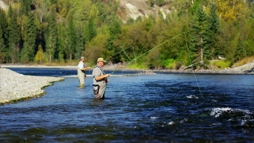 Fisherman fly fishing in Canadian river casting using rod and reel #14712250