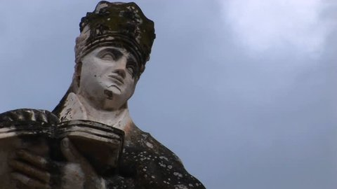 A cloud time lapse moving above a statue of a woman holding a book.