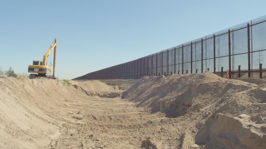 Wide of a trench near the border fence with heavy equipment in frame.