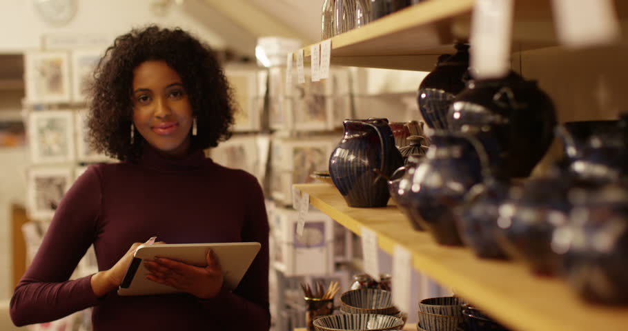 Young woman inspecting quality of the ceramics in her shop. Royalty-Free Stock Footage #14730478