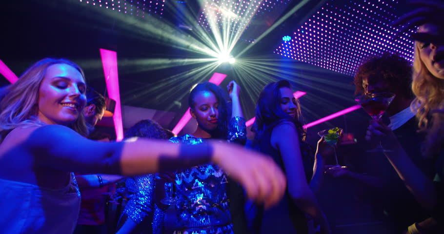 Attractive African-American woman dancing with cocktail in her hand during party, laughing at her girl friends on the dance floor at a modern disco nightclub.
