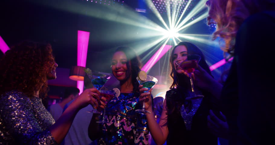 Women dancing in Slow Motion and drinking cocktails with her multicultural group of girl friends on the dance floor, laughing and enjoying the music and party in the nightclub.