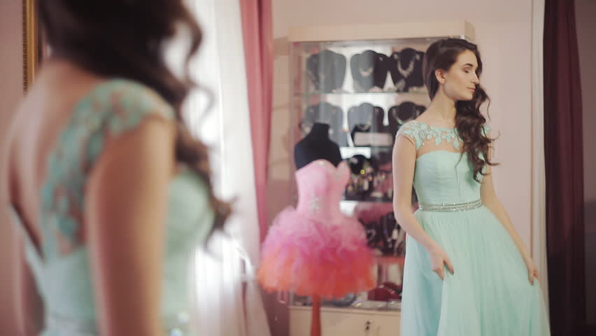 Young beautiful woman chooses a dress in the salon for graduation ball | Shutterstock HD Video #14732074