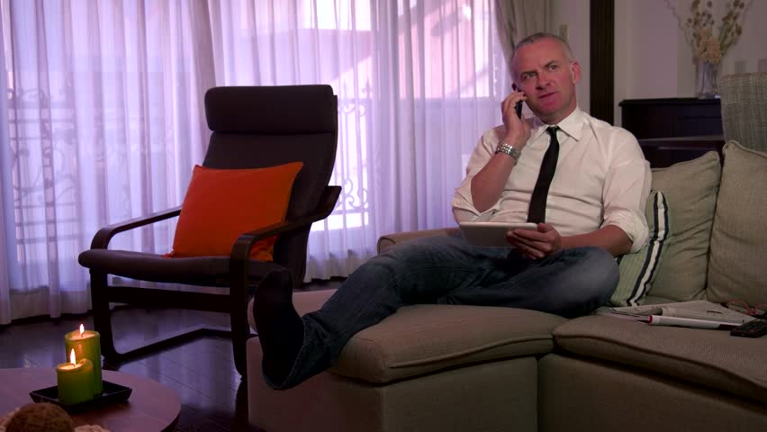 People working at home, business man sitting on sofa with ipad tablet computer, reading news, businessman talking on cell phone, busy male manager on couch, worker speaking with mobile telephone | Shutterstock HD Video #14732914
