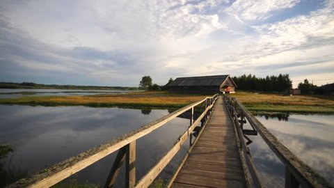 Crossing the wooden walking bridge over the small river. Clouds beautifully reflect in water. Russian National park Kenozero, Vershinino village.
