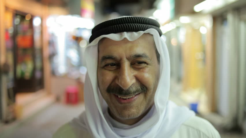 Bahrain - 2011 - Portraits of two smiling Bahraini men looking directly into camera, wearing traditional Arab clothes of Abaya and Keffiyeh.  Shot taken in a market or souk at night.