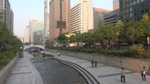 SEOUL, SOUTH KOREA - 8 OCTOBER 2015: People walk past a stream in central Seoul