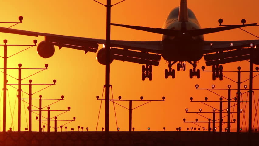 HD footage of a 4 engine jumbo jet plane landing in silhouette against an orange sunset sky, followed by a defocus / camera blur out.  Jet engine audio included.