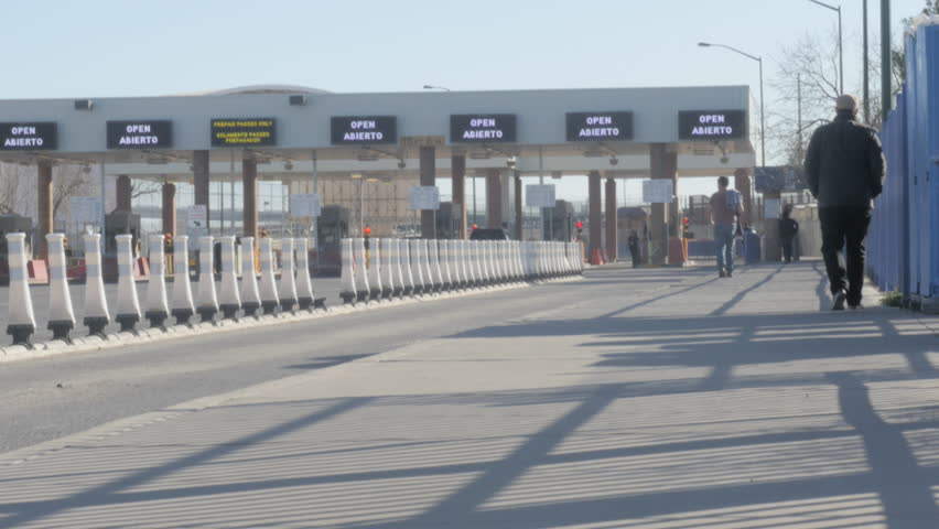 4K shot of people walking toward the US and Mexico border crossing in the daytime.