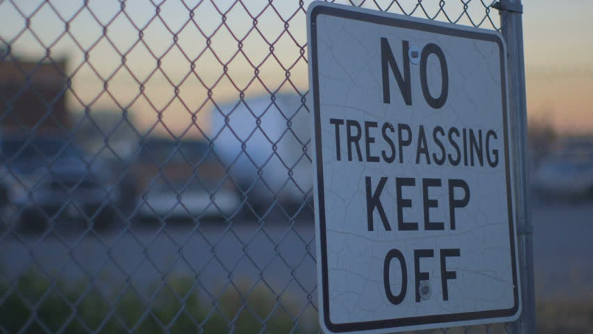 Pan shot of No Trespassing Keep Off Sign on a fence near the border.