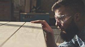 Carpenter checks the quality sanding wooden board. RAW video record.