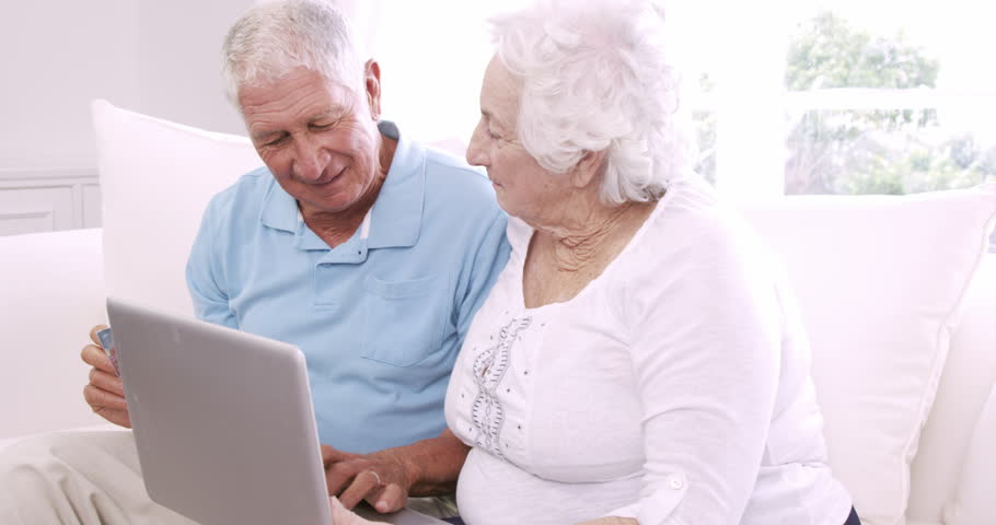 Smiling senior couple using laptop on the sofa | Shutterstock HD Video #14778421
