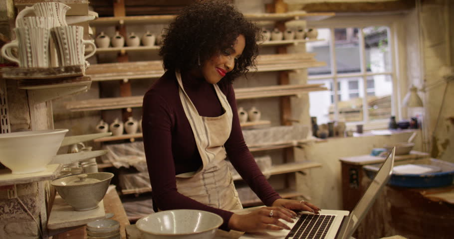 Young attractive woman using laptop at a pottery studio. #14790118