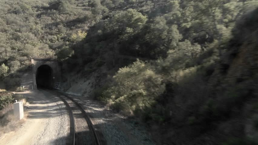 An exciting point of view shot from the front of a train going through many tunnels at high speed.