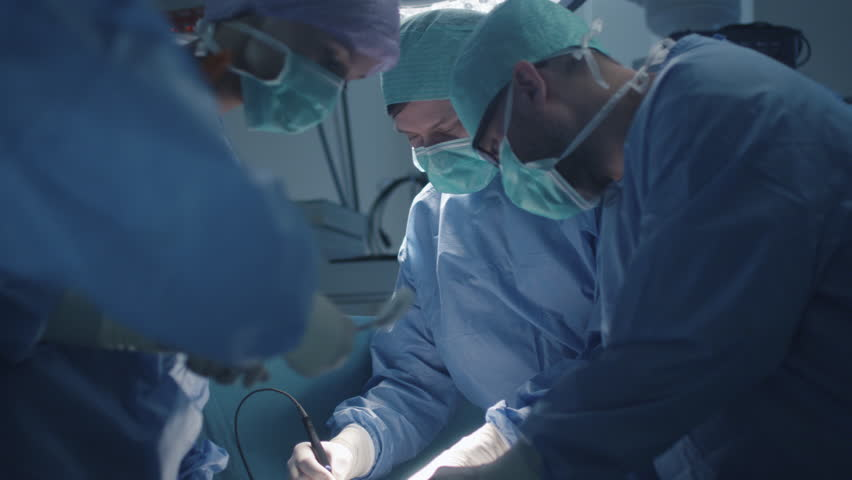 Medical Team Performing Surgical Operation in Modern Operating Room. Shot on RED Cinema Camera.