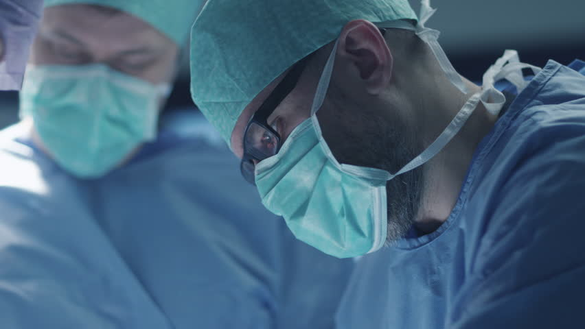 Portrait of Focused and Concentrated Surgeon Performing Surgical Operation in Modern Operating Room. Shot on RED Cinema Camera.
