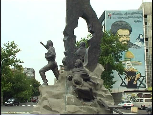 Tehran, Iran - 2005 - Shot of a monument of the Iranian Revolution. Behind the monument is a poster of Abbas al-Mousawi (co-founder of Hezbollah), a Palestinian fighter and the Al Aqsa Mosque.