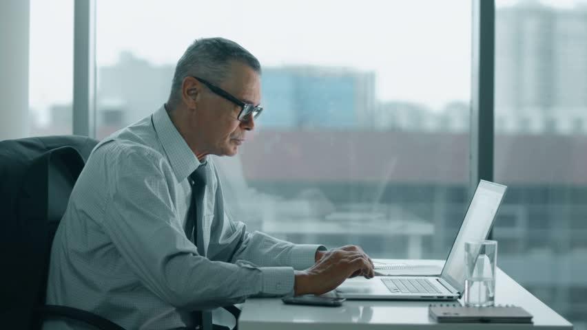 Elderly businessman working with computer in modern office   Shutterstock HD Video #14813083