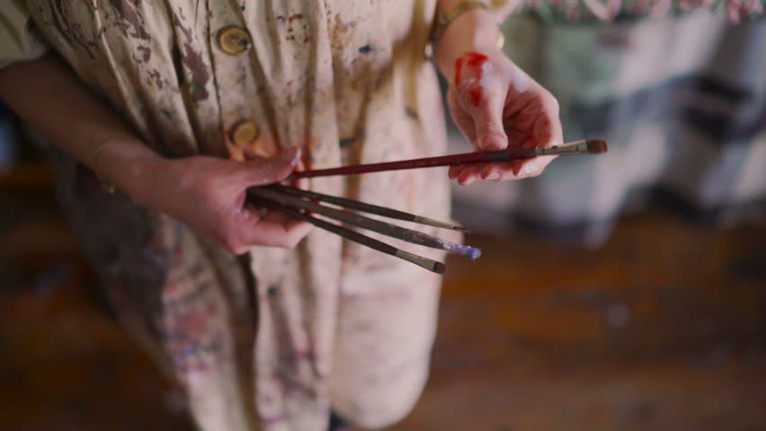 Cropped closeup of the hands of an artist that have paint on them, wearing an artist's smock and holding some well-used paintbrushes | Shutterstock HD Video #14819002