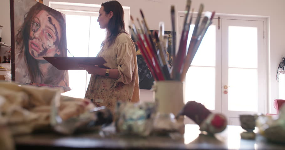 Profile shot of a young woman artist working in a real and messy brightly lit studio painting with fine brush on a canvas with beautful light coming in through a window